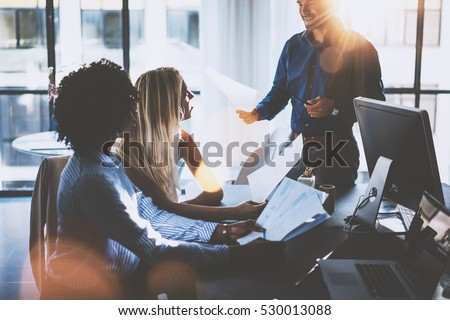 Young team of coworkers making great meeting discussion in modern coworking office.Hispanic businessman talking with two beautiful womans.Teamwork process.Horizontal,blurred background,sun effect