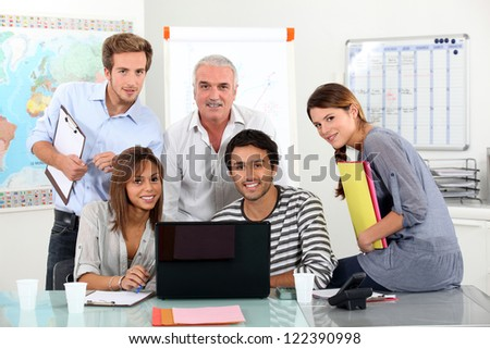 Young team of people sitting around a laptop with an older guy - stock photo