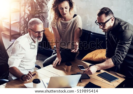 Young team of successful businessman found a great creative solution in modern coworking studio.Bearded man talking with colleagues about startup project.Business people brainstorm concept.Horizontal