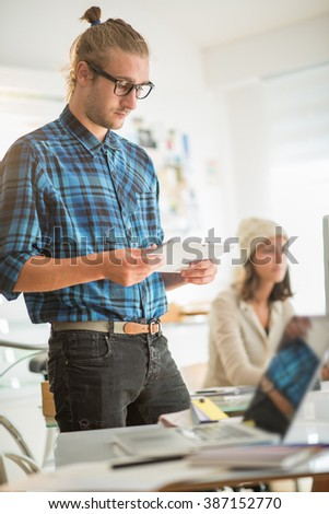 Young team working at office, focus on a young man standing and using a tablet. The office is bright and modern. Shot with flare