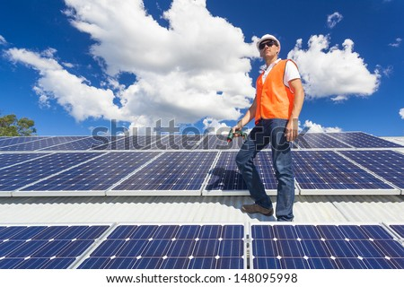 Young technician checking solar panels on factory roof - stock photo