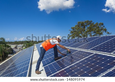Young technician installing solar panels on factory roof - stock photo