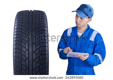 Young technician with a blue uniform, using a digital tablet to control a tire - stock photo