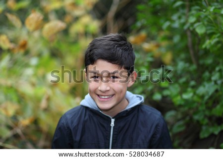 Young teen boy playing among the trees in the countryside