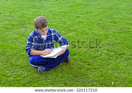 Young Teen Boy with Sketch Pad Drawing  or Writing While Sitting on Grass Outdoors, with Copy Space - stock photo