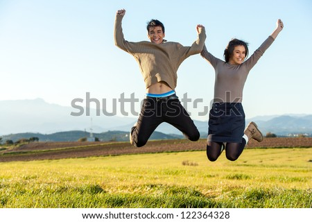 Young teen couple having fun jumping outdoors. - stock photo