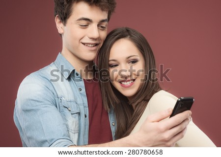 Young teen couple having fun together with a smart phone