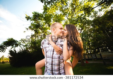 young teen couple in love having fun and enjoying the beautiful nature in park - stock photo