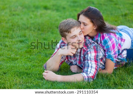 Young teen couple on the green grass in the park.