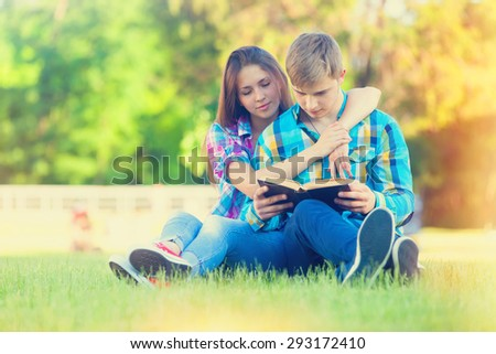 Young teen couple with notebook on the green grass in the park.