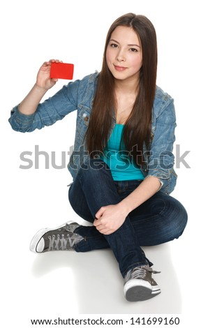 Young teen female sitting on floor showing blank credit card, isolated on white - stock photo