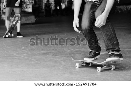 Young teen friends on skateboard in graffiti skate park  - stock photo