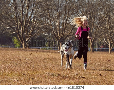 Young teen girl and her dog running playing in open field