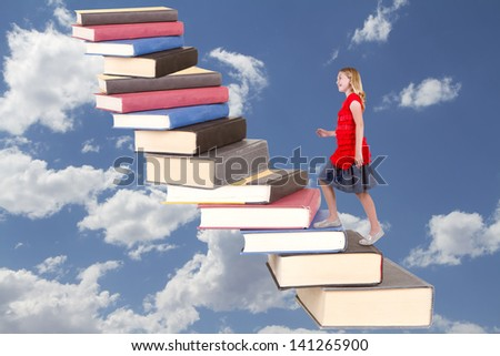 Young teen girl climbing a staircase of book with a cloudy sky background - stock photo