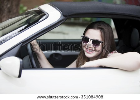 Young teen girl driving a car - stock photo