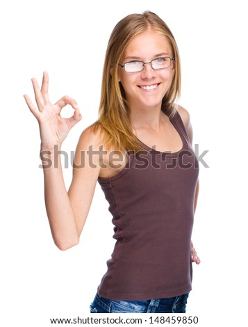 Young teen girl is showing OK sign, isolated over white - stock photo