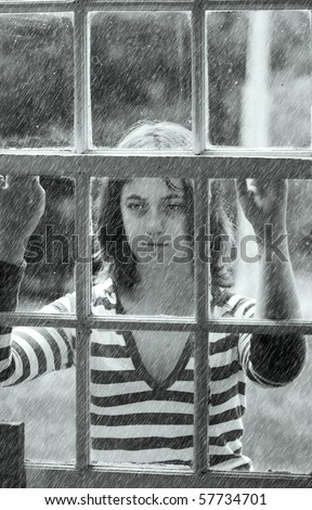 Young teen girl looking out the rainy window feeling depressed.