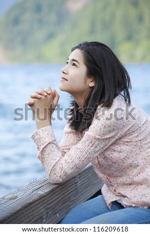 Young teen girl sitting quietly on lake pier, praying - stock photo
