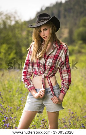 Young teen girl wearing cowboy hat and red flannel shirt posing outdoors - stock photo