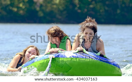 Young teen girls on a tube behind a boat, one is trying to climb up.