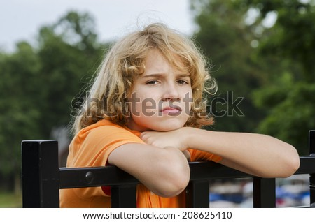 Young teen is sitting around bored in the Summer - stock photo