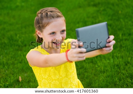 Young teen is taking a selfie in a park while having a walk. Green grass in the background. The young fancier of technology progress. Perfect retouching. - stock photo