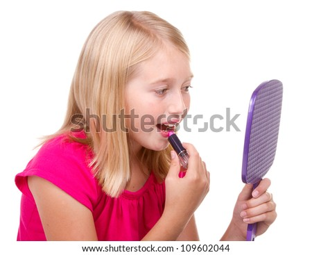 Young teen putting on lipstick isolated on white