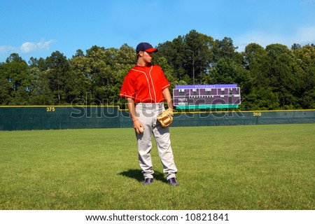 Young teen stands on the baseball field with glove and ball in hand.  Scoreboard stands in background. - stock photo