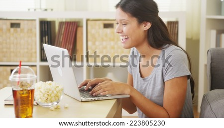 Young teen using laptop and smiling - stock photo