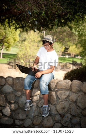 young teen  with laptop sitting on rock