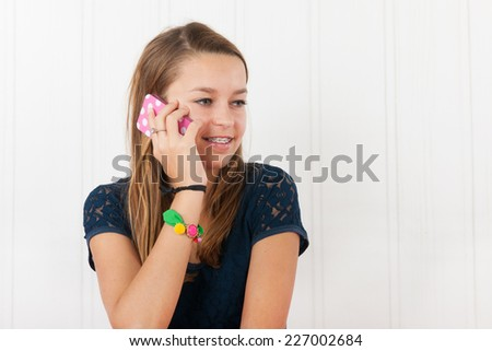 Young teen with smartphone talking and having fun