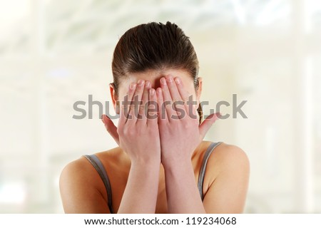 Young teen woman covering her eyes