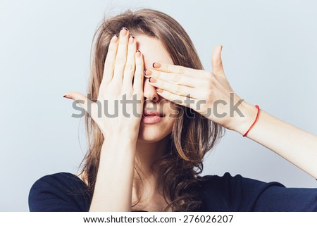 Young teen woman covering her eyes isolated on a gray background