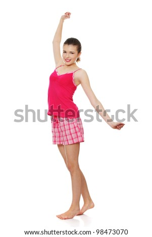 Young teen woman in pink pajamas isolated on white background