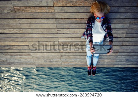 Young teen woman relaxing upon a wooden jetty while taking self portrait holding up tablet, female tourist making remembering portrait during her holidays, surrealistic photo, filter, cross process - stock photo