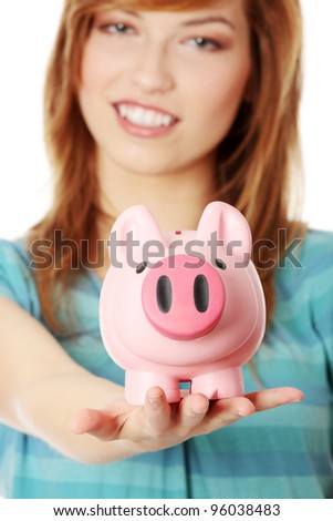 Young teen woman showing her pink piggy bank, isolated on white background