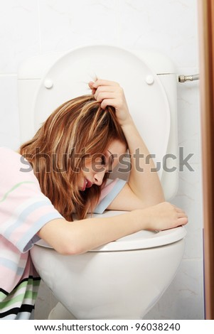 Young teen woman vomiting in toilet - stock photo