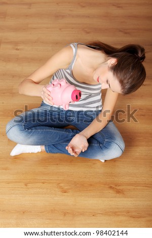 Young teen woman with her pink piggy bank