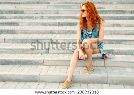 Young teen women sitting on stairs on her skateboard and looking away. A lot of copyspace. Urban fashion shot. Summer street fun. - stock photo