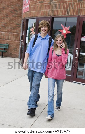 Young teenage boy and girl holding hands while walking and the girl is talking on cell phone outside of a school building - stock photo