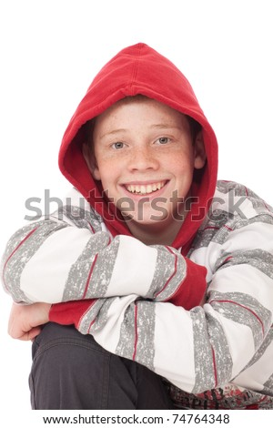 Young teenage boy kneeling with crossed arms and red hood - stock photo