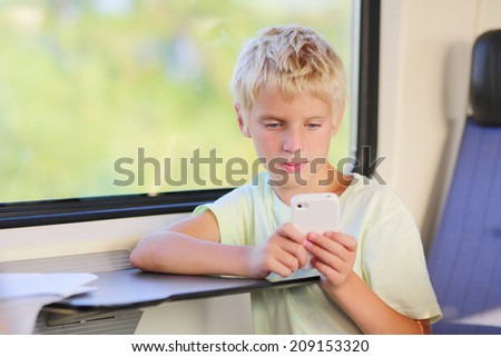 Young teenage boy travelling to school by train sitting in wagon coach sending text message to somebody using his mobile phone