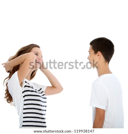 Young teenage couple talking with the girl flicking her her and laughing flirtaceously isolated on white