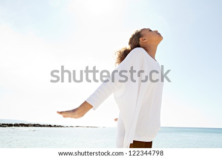 Young teenage girl breathing fresh air while standing by the sea with her arms outstretched and with her head leaning back against a blue sky. - stock photo