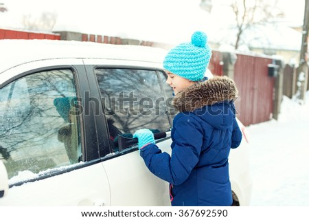 Young teenage girl cleaning white car from winter snow in january. Bright outdoors horizontal image - stock photo