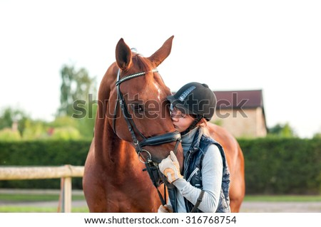 Young teenage girl equestrian kissing her chestnut horse. Multicolored outdoors horizontal image. - stock photo
