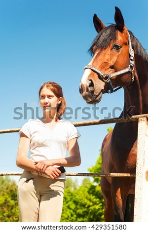 Young teenage girl equestrian standing close to big chestnut horse. Vibrant summertime outdoors vertical image. - stock photo