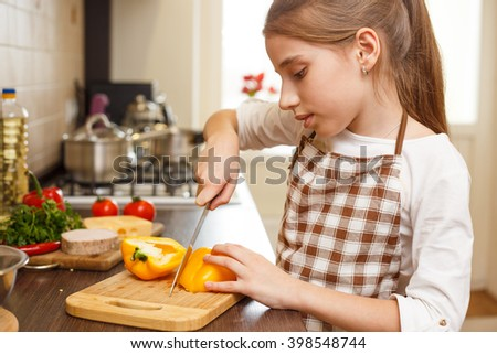 Young teenage girl in apron cutting sweet pepper on board at the kitchen.  - stock photo