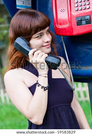 Young teenage girl in telephone box - stock photo