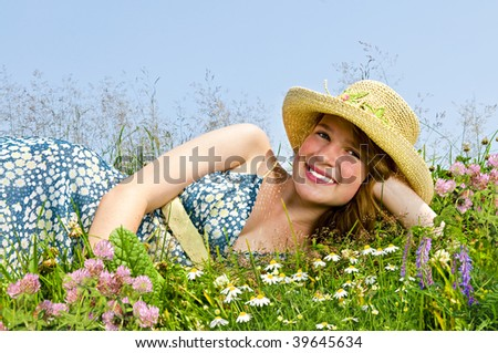 Young teenage girl laying on summer meadow amid wildflowers in straw hat